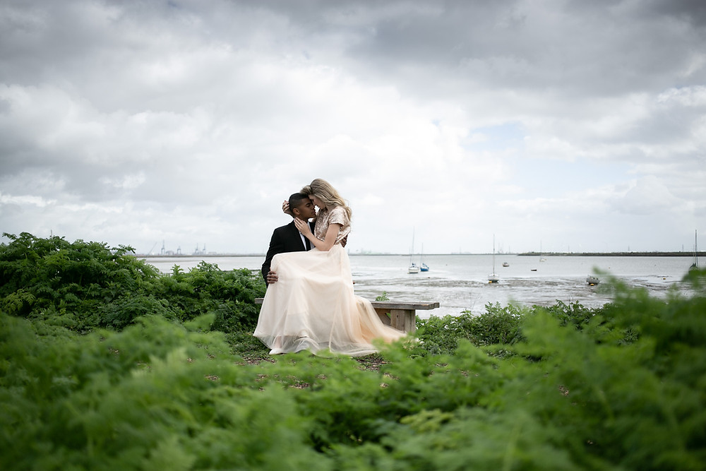 © Photographed by John Knight | Bride sitting on groom's lap on bench overlooking boats