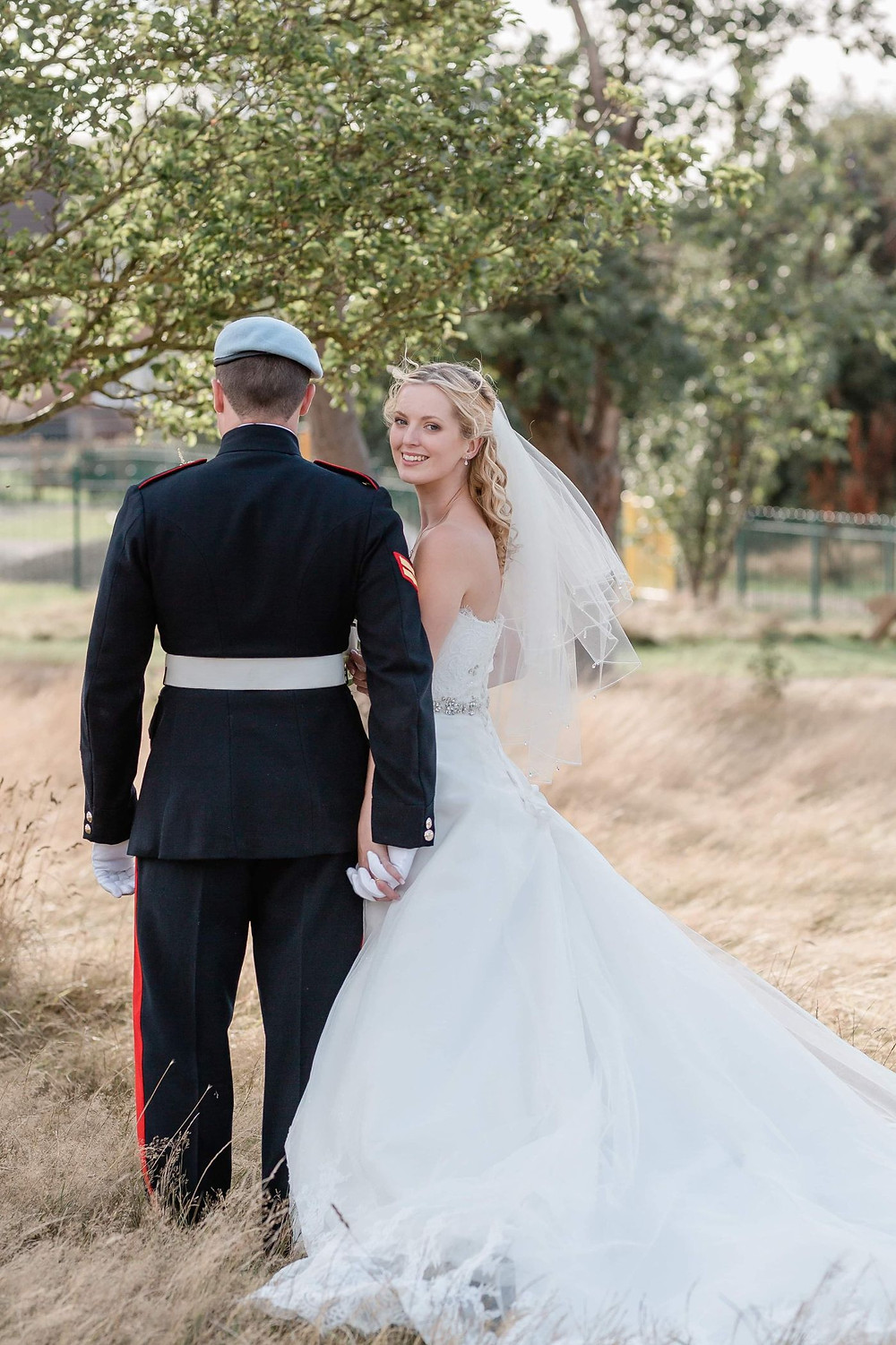 Kate Hennessy Photography | Bride looking at camera over groom's shoulder, bride and groom standing in a field, military wedding
