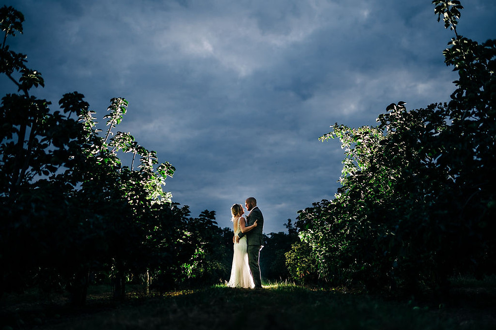 TJG Photography | Evening night-time shot bride and groom in an orchard