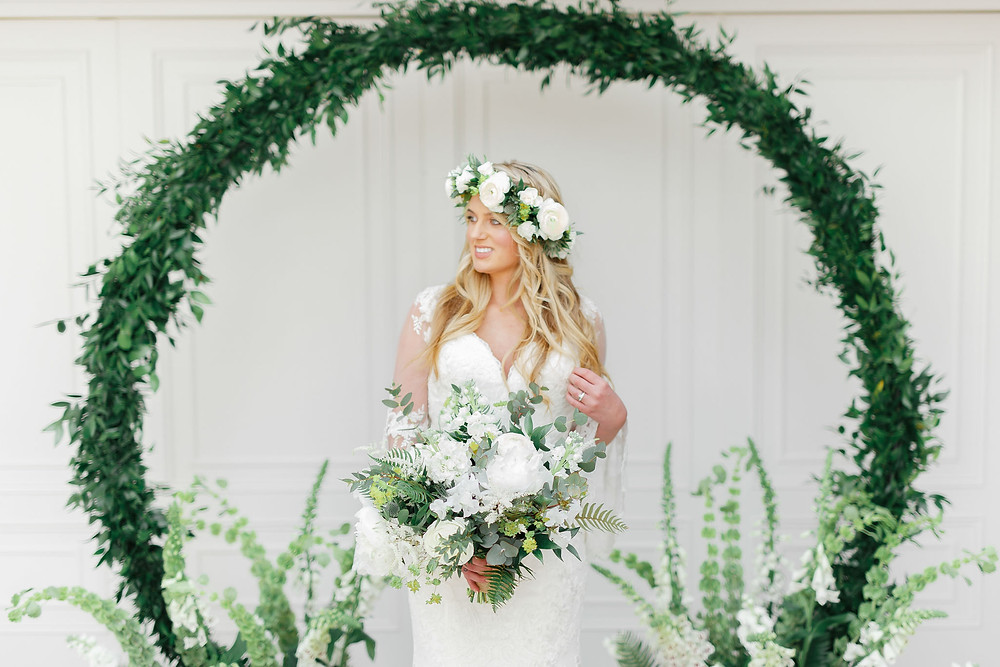 White Stag Wedding Photography | Bride standing in front of green foliage moongate, moon arch, green and white wedding