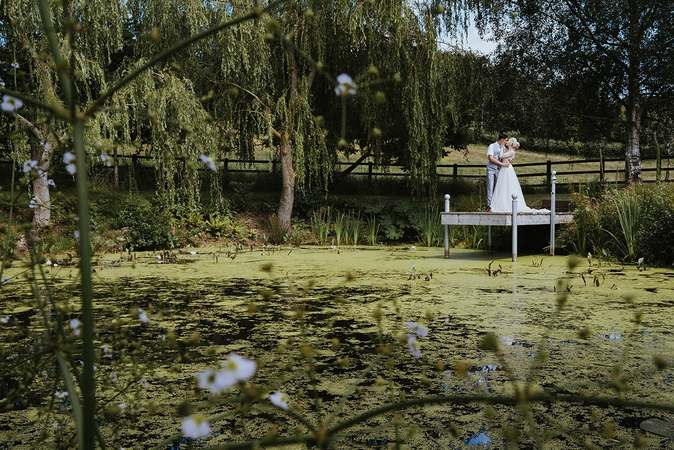 Eco-friendly wedding venue The Oak Barn, bride and groom standing on pontoon by lake