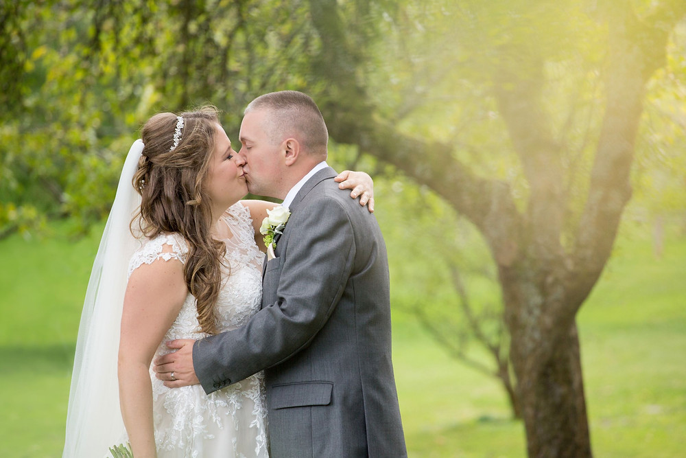 Helen England Photography | Bride and groom kissing by a tree