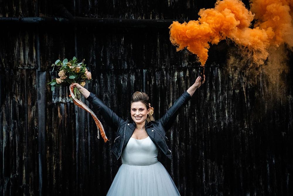 James Grist Photography | Bride wearing leather jacket holding orange smoke bomb