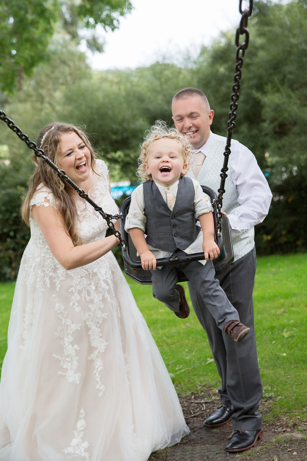 Helen England Photography | Bride and groom pushing son on a swing