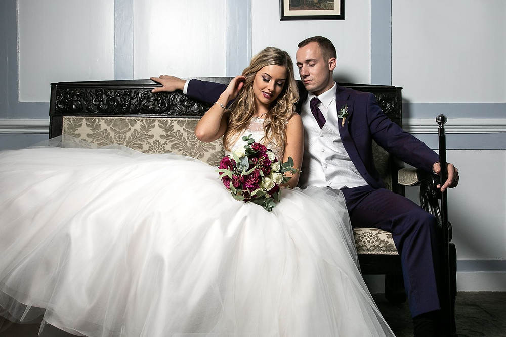 Bride and groom relaxing on ornate antique sofa