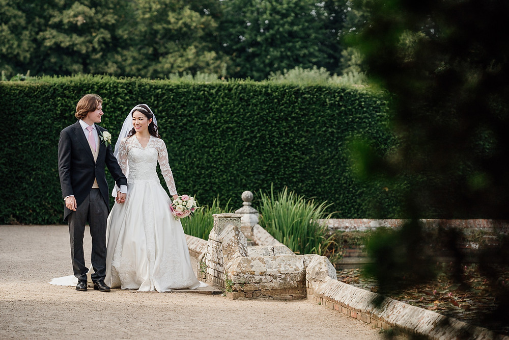 Penny Young Photography | Bride and groom walking in gardens at Penshurst Place