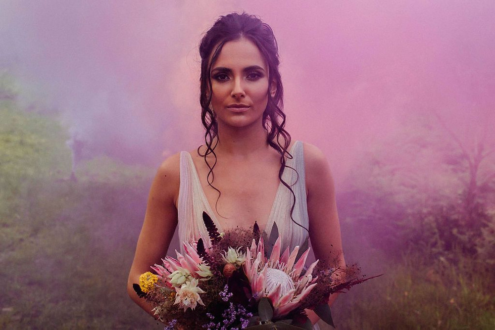 Sammy Taylor Wedding Photography | Pink and purple smoke bombs around stunning bride in colourful wedding dress and boho flowers
