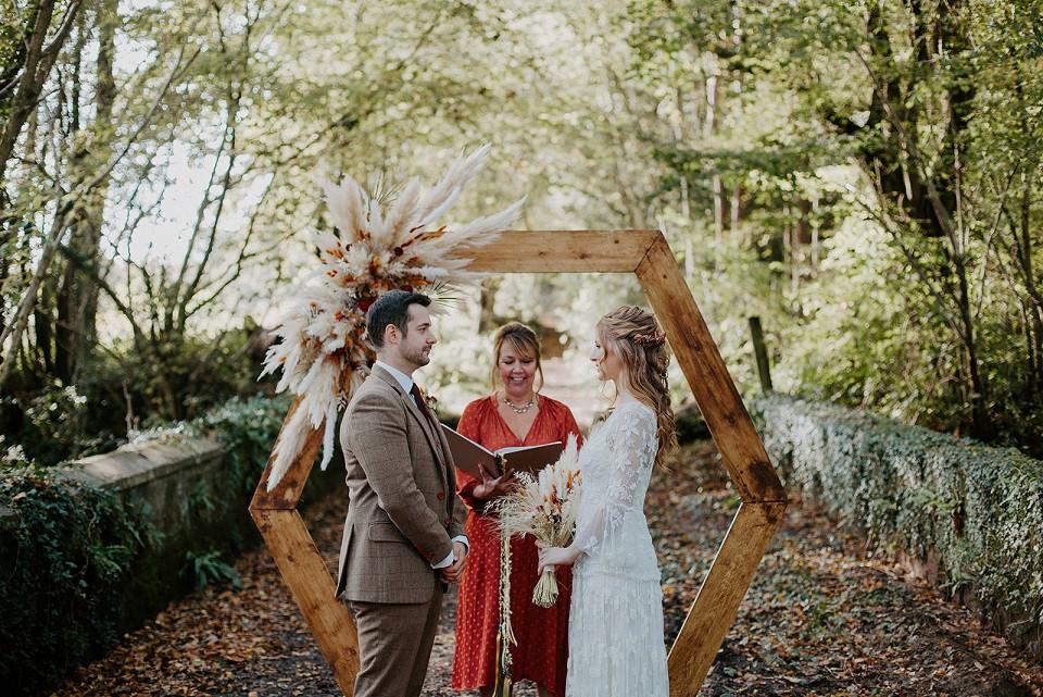 Ashleigh Joy Photography | Autumn wedding, bride and groom at altar, pampas on wooden frame, woodland wedding