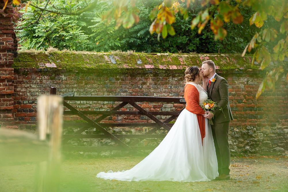 Helen England Photography | Autumn wedding, bride and groom kissing, orange wedding flowers, bride wearing orange wrap shawl