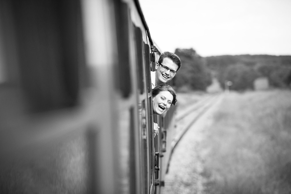 Black and white image of bride and groom leaning out of a window on a moving train