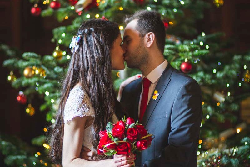 Emma Migden Photography | Bride and groom kissing in front of Christmas tree, red rose wedding bouquet, Christmas wedding