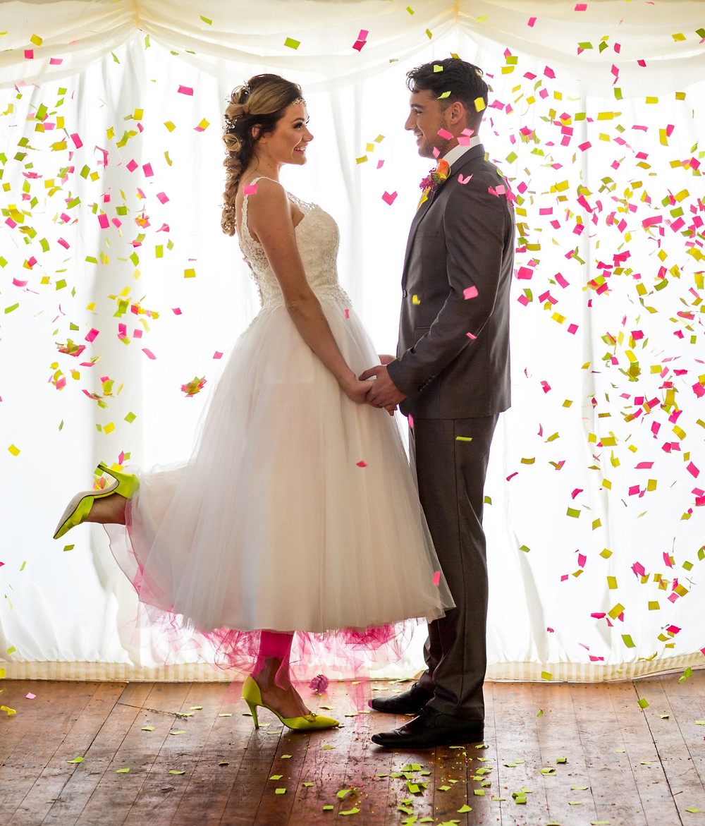 Jeff Oliver Photography | Bride and groom standing under neon confetti, bride wearing yellow shoes, bride wearing pink underskirt