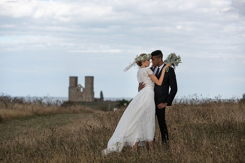 Tony Pullen Photography | Bride and groom standing in field in front of historic ruins of Reculver Towers