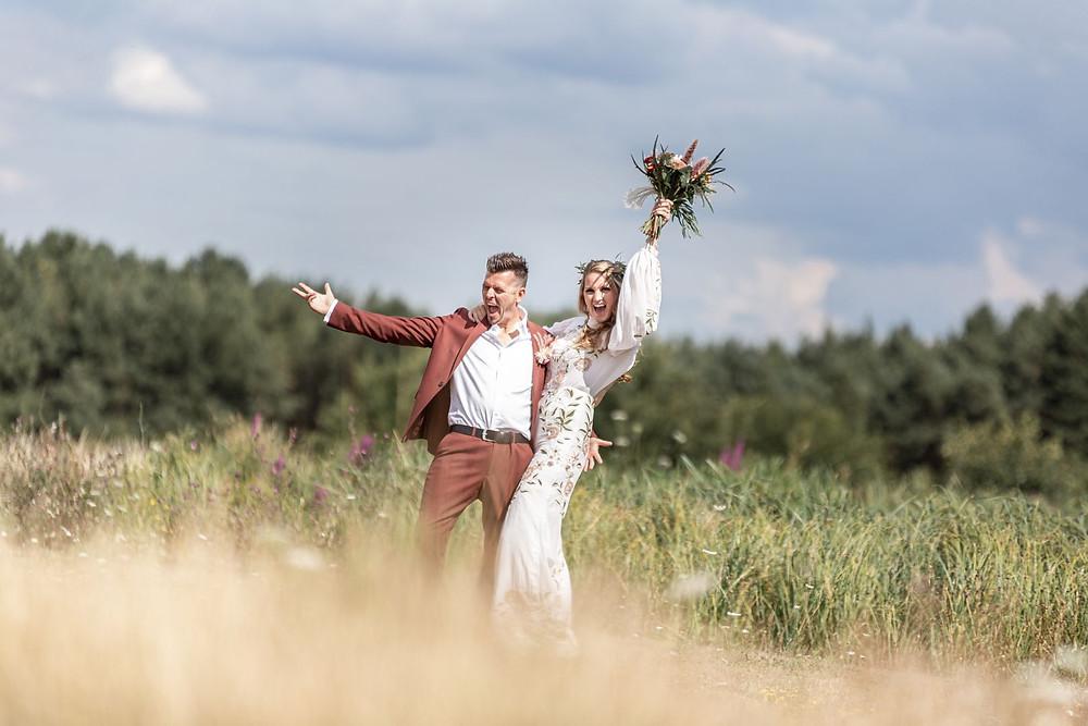 © AlisonWonderland Photography | Boho bride and groom celebrating wedding, bride wearing bridal jumpsuit, holding up rustic bouquet