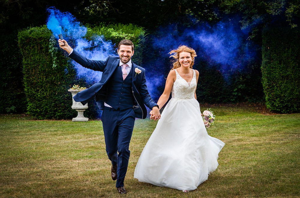 James Grist Photography | Bride and groom running with blue smoke bomb