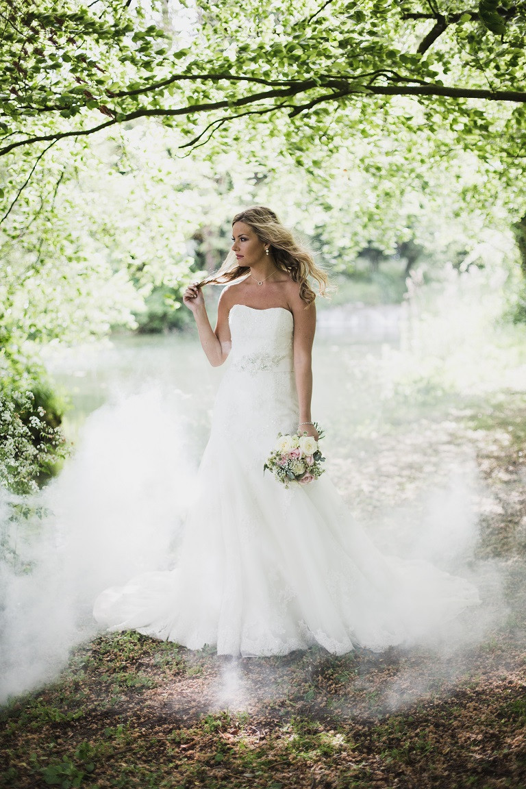Photographed by John Knight | Bride standing undeneath trees, in dappled light with white smoke on the floor, smoke-bomb