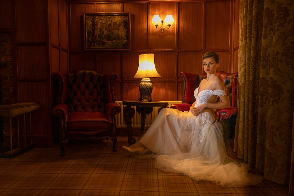 Jeff Oliver Photography | Bride sitting in red leather chair in wood-panelled room at Knowle Country House, Victoria's Bridal Boutique dress