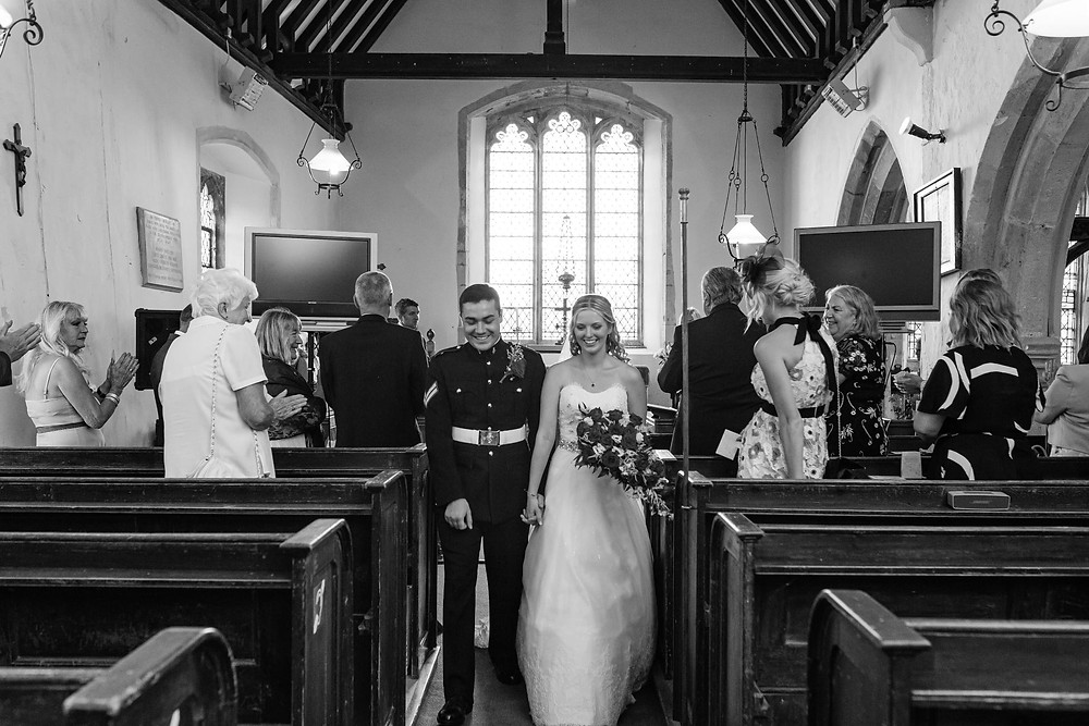 Black and white image of bride and groom leaving church after wedding ceremony