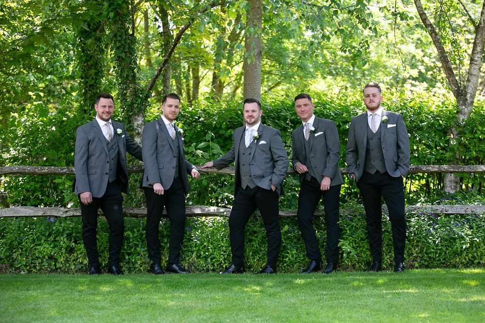 Groom and groomsmen standing by a fence
