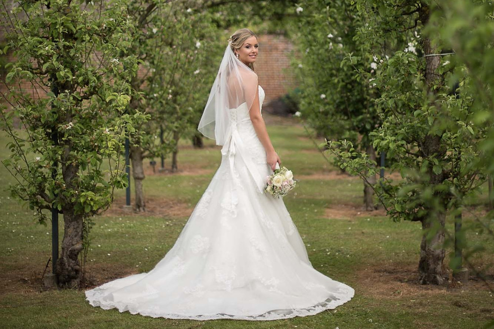 Bride standing in an orchard