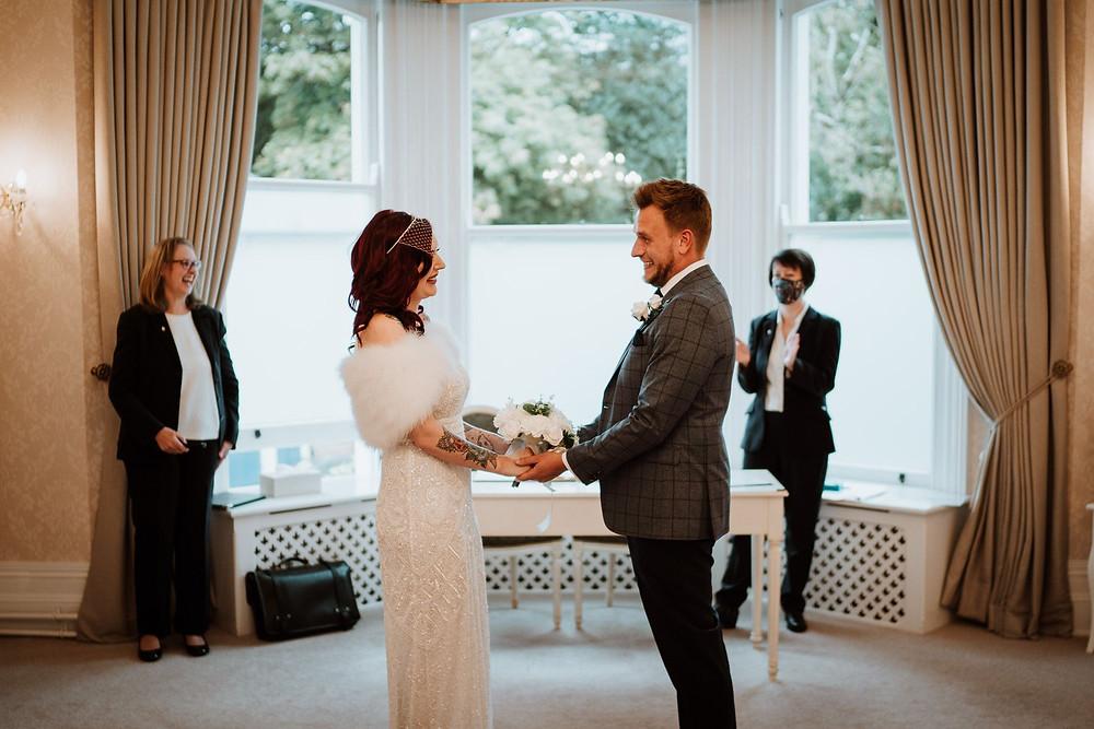 Bride and groom having wedding ceremony in registry office