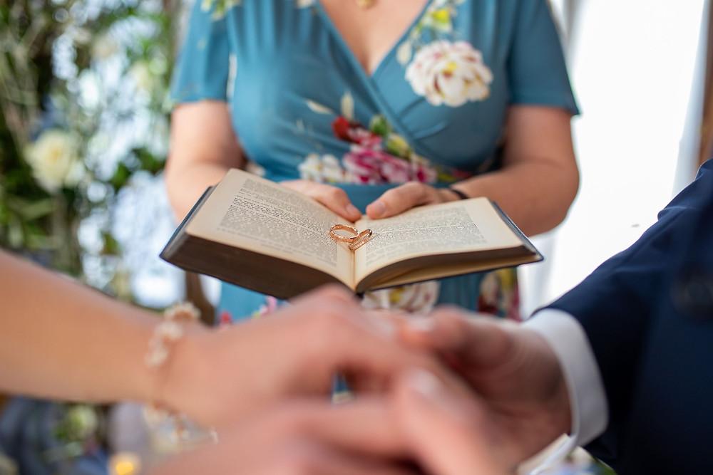 Celebrant-led wedding, wedding rings on an open book