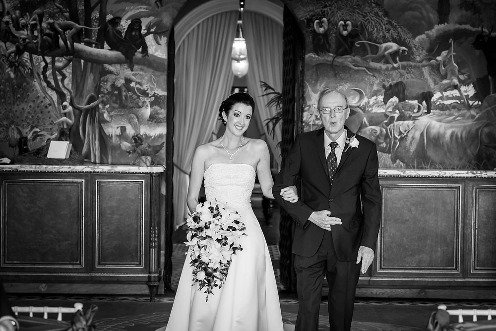 Black and white shot of bride walking up the aisle with her father