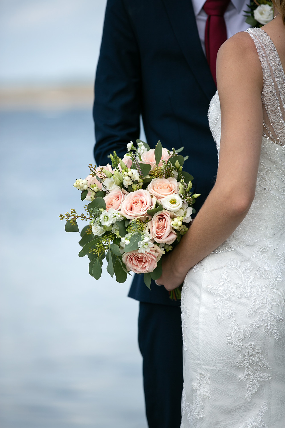 Bride and groom holding pink and cream bouquet of flowers