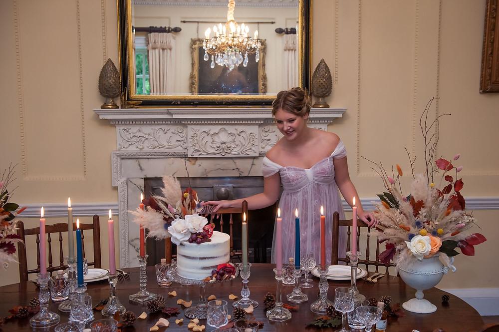 Kat Forsyth Photography   Bride overseeing wedding breakfast set-up, pastel candles, boho floral arrangements, Regency Wedding, Autumn Wedding Inspiration, Jane Austen Wedding, Bridgerton Wedding