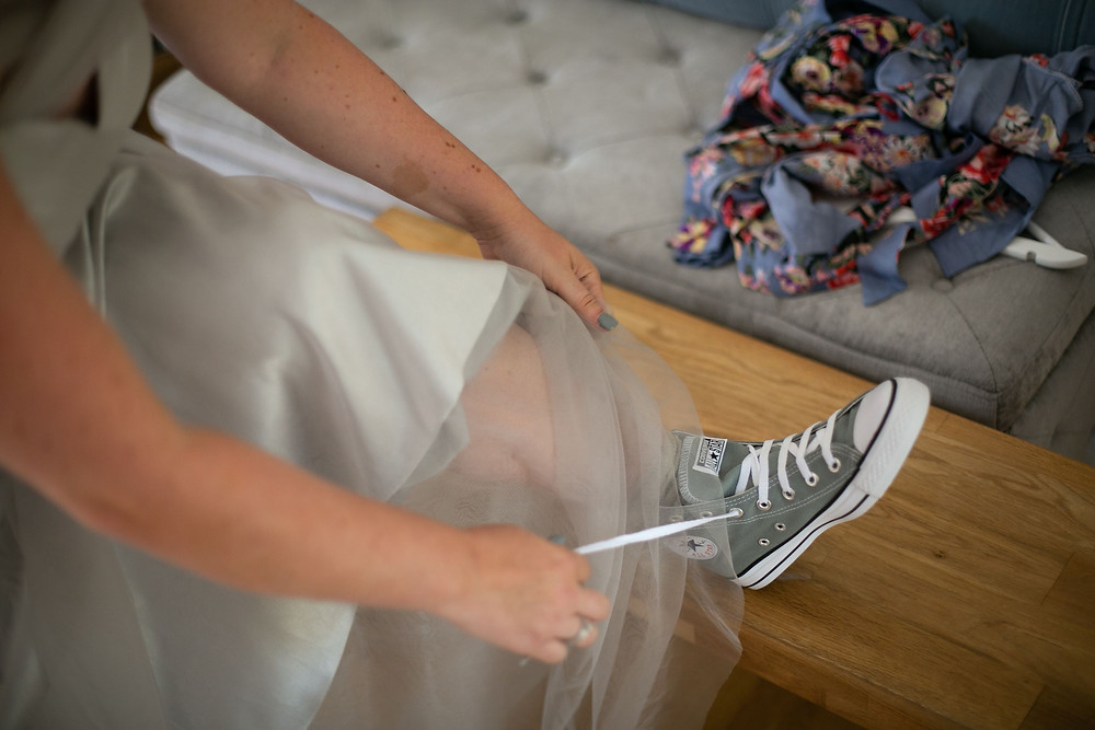 Bride putting on grey Converse