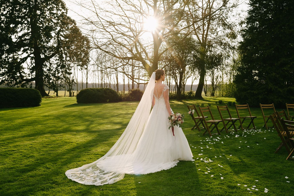 Michael Newington Gray Photography | bride walking towards circular aisle with stunning wedding dress and long veil with lace details