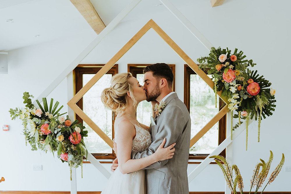 Barn Wedding | Luxury Wedding | Bright Light Wedding | Bride and groom kissing in front of unique square frame backdrop