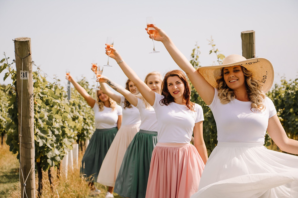 Wild Meadow Photography | Women in vineyard holding glasses of wine, hen-do ideas in Kent