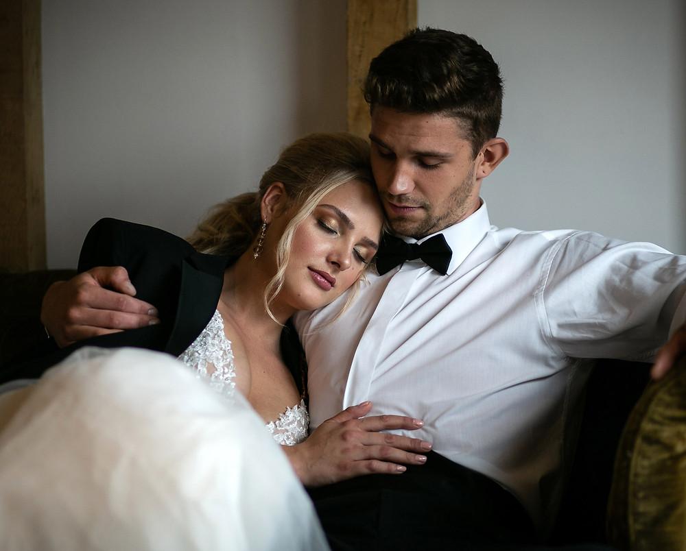 Bride and groom cuddling on sofa