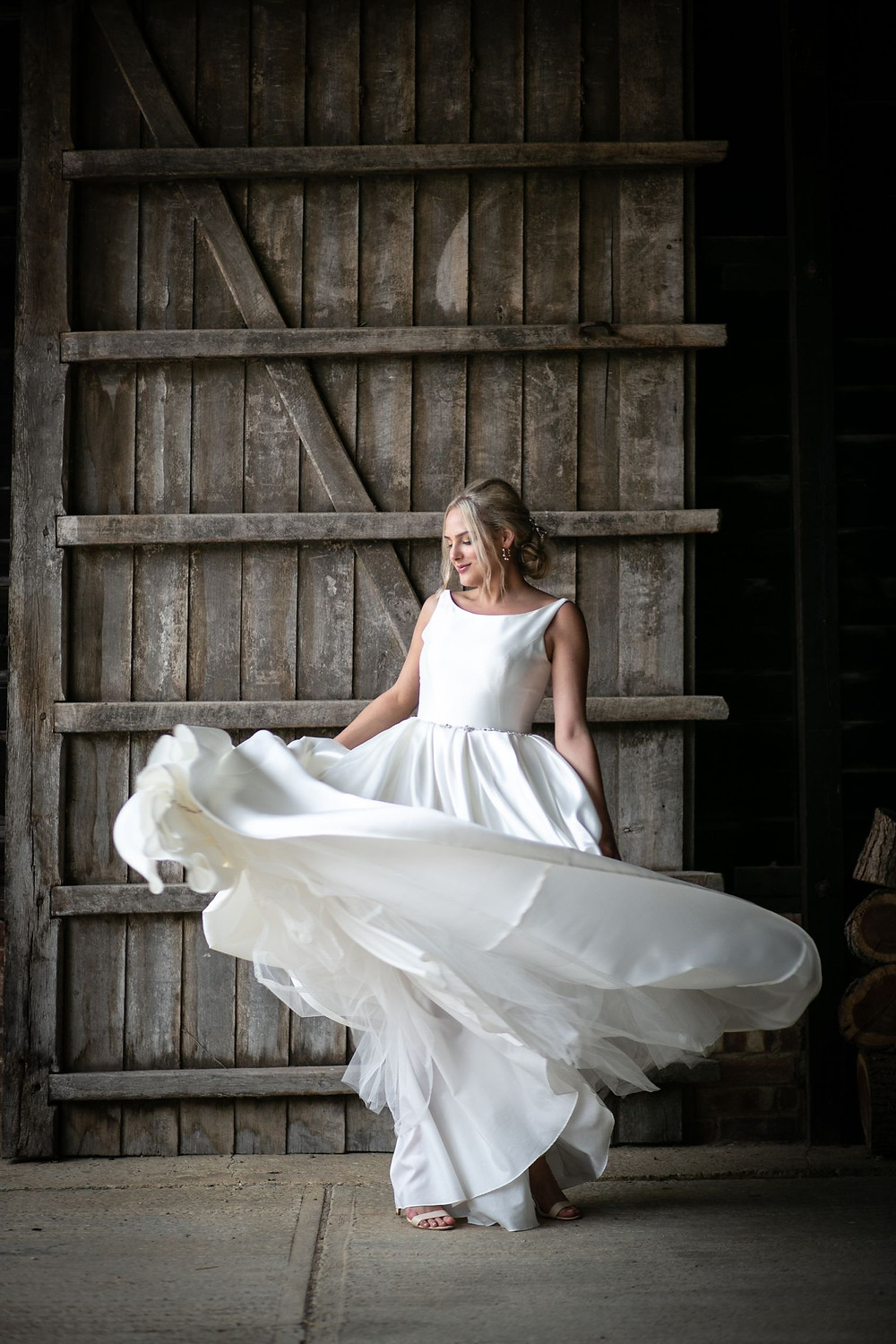 Photographed by John Knight | Bride spinning in wedding dress in front of big wooden door