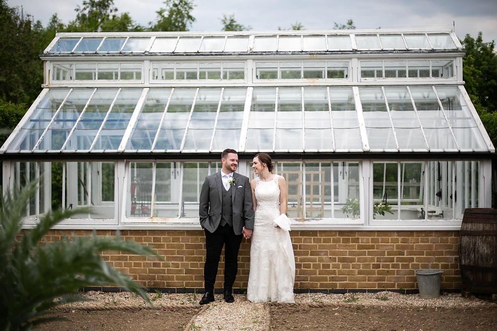 Bride and groom standing in front of greenhouse