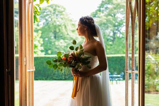 Matt & Kizzy Wedding Photography | Bride standing in open doorway wearing strapless wedding dress, holding eucalyptus bouquet
