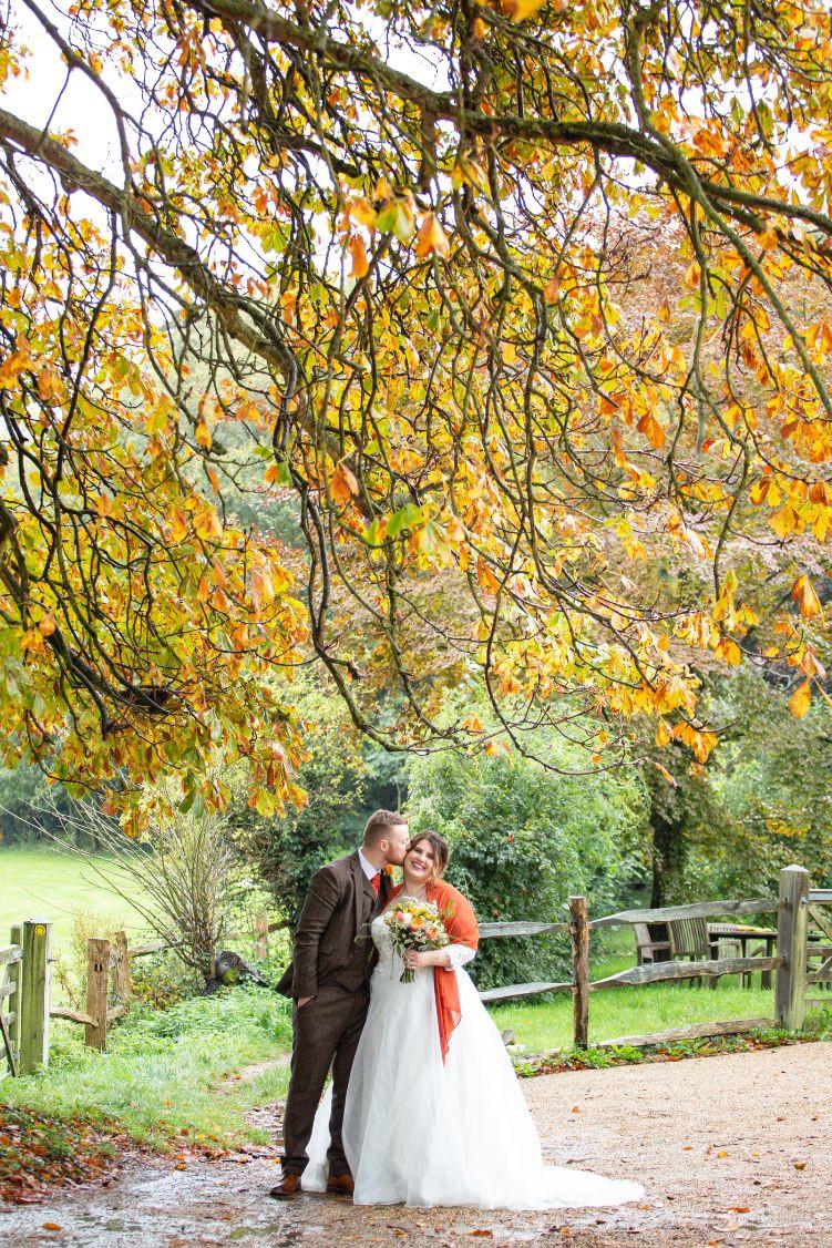 Helen England Photography | Bride and groom standing under tree, autumn wedding