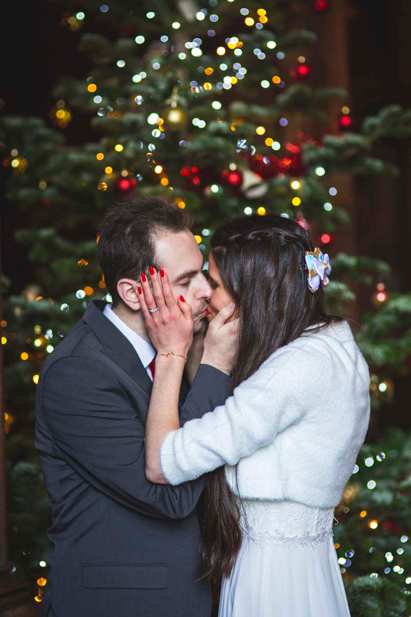 Emma Migden Photography | Bride and groom kissing in front of Christmas tree