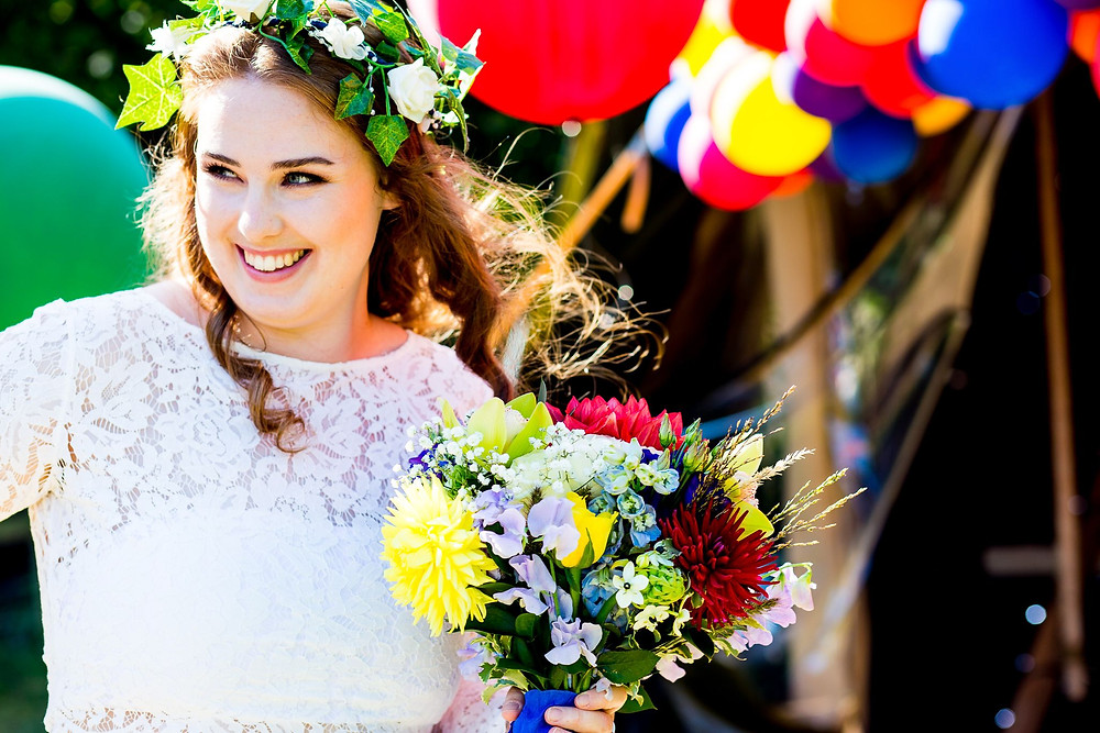 Strawberry Photography | Bright image of bride wearing informal flower crown with spring bouquet flowers and bright balloons in background