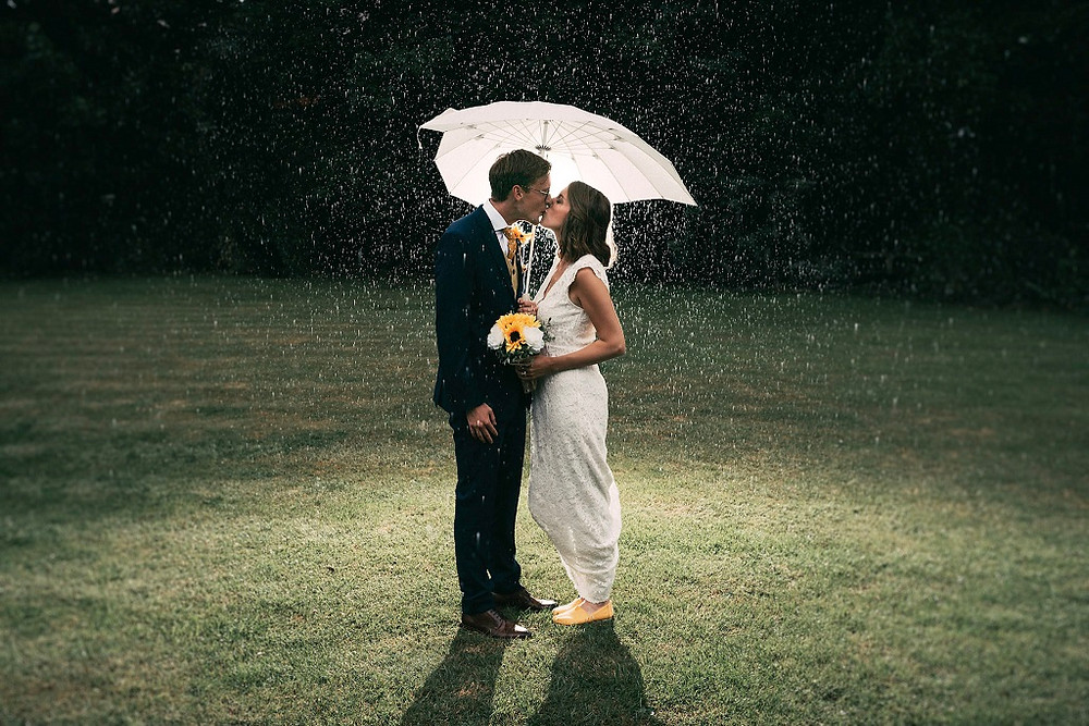 Tom Cullen Photography | Bride and groom holding an umbrella kissing in the rain