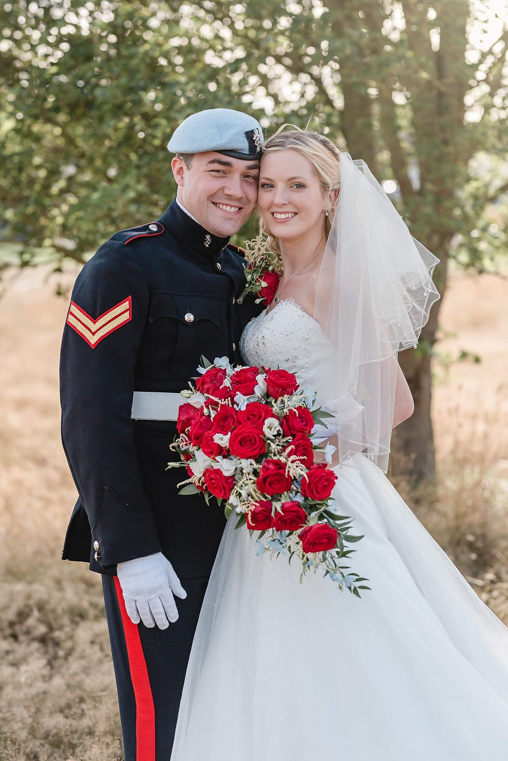 Kate Hennessy Photography | Bride and groom standing in front of a tree, holding bouquet of red roses