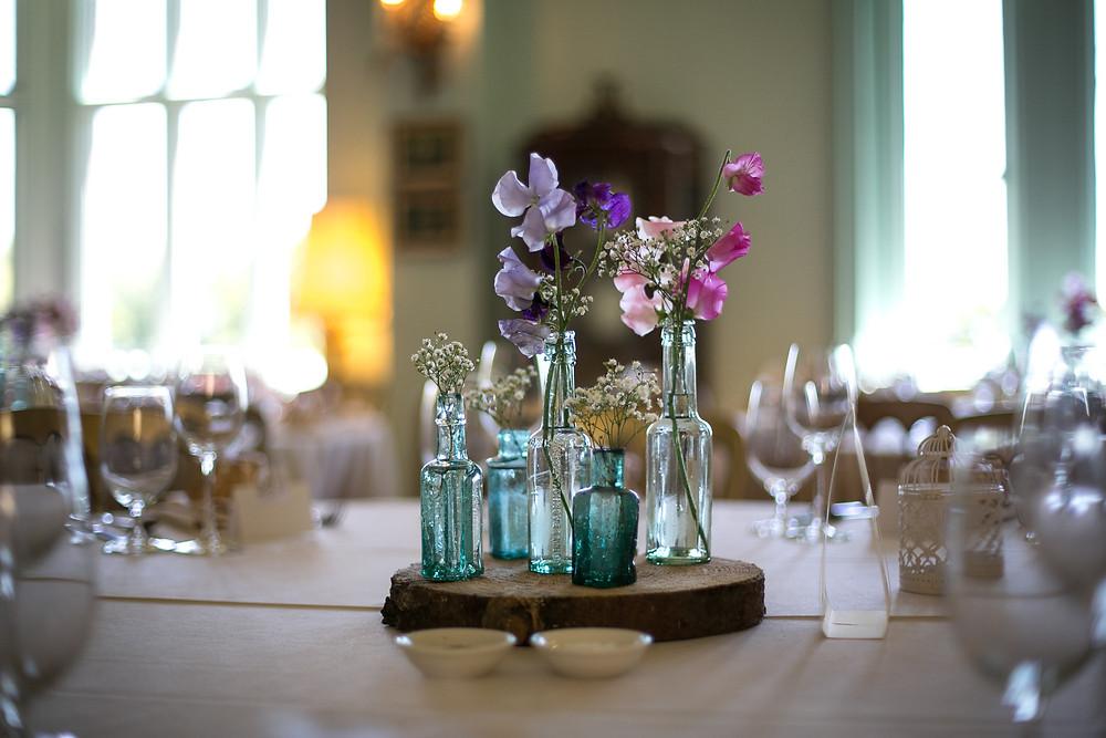 Flowers in jars on wood slice wedding centrepiece