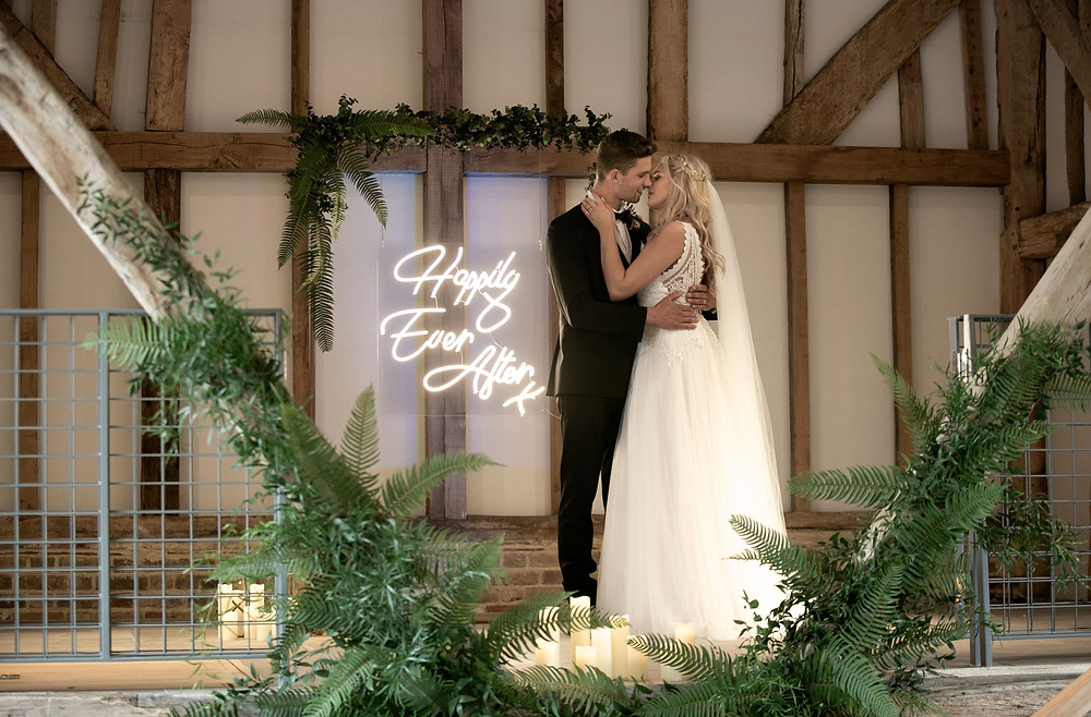 Photographed by John Knight | Bride and groom kissing by neon 'happily ever after' sign at The Oak Barn, Kent