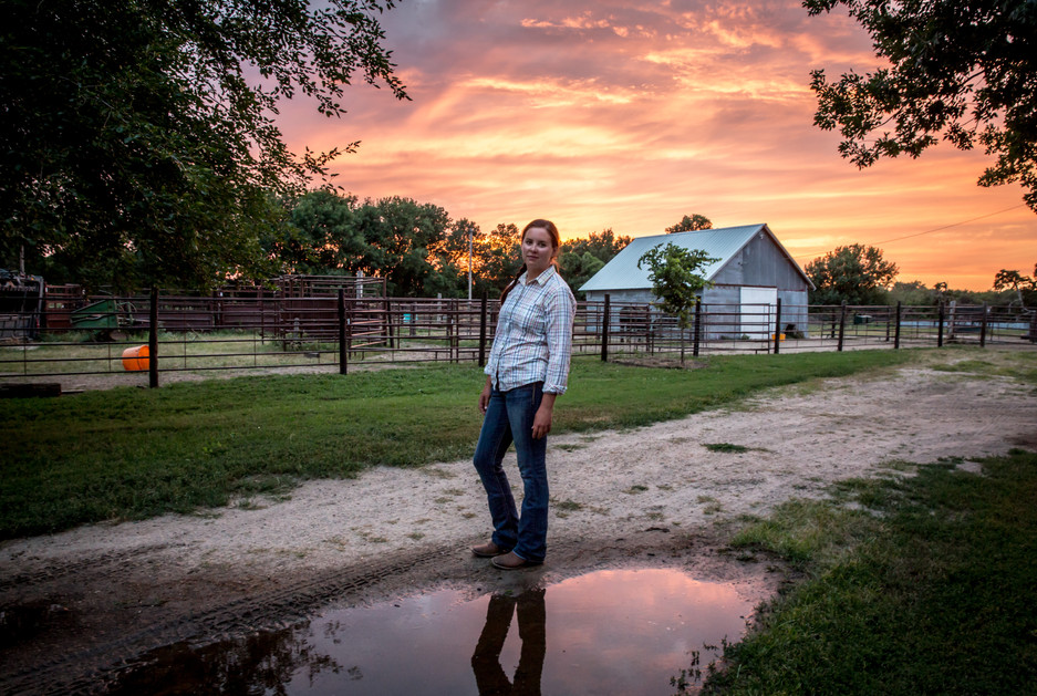 After completing her nightly chores, Meghan Hammond pauses briefly under a brilliant July sunset before heading back home for the night.