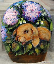 lop eared bunny in the flowers painted on a rock,handpainted rocks,lop eared bunny painting,original rabbit painting