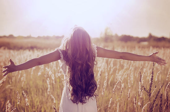 Autumn Girl enjoying nature on the field. Beauty Girl Outdoors raising hands in sunlight r