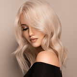 Beautiful girl with hair coloring in ultra blond. Stylish hairstyle curls done in a beauty