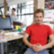 Homme souriant, assis à son bureau de travail
