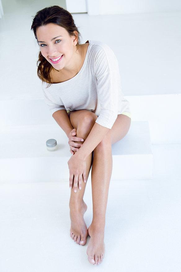 Body care. Woman applying cream on legs.